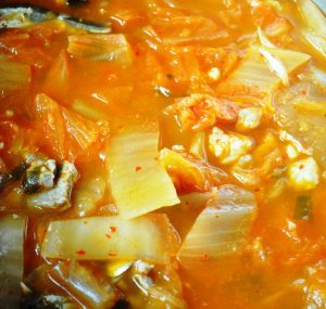 Kimchi Jjigae ready to cook in pot with everything added
