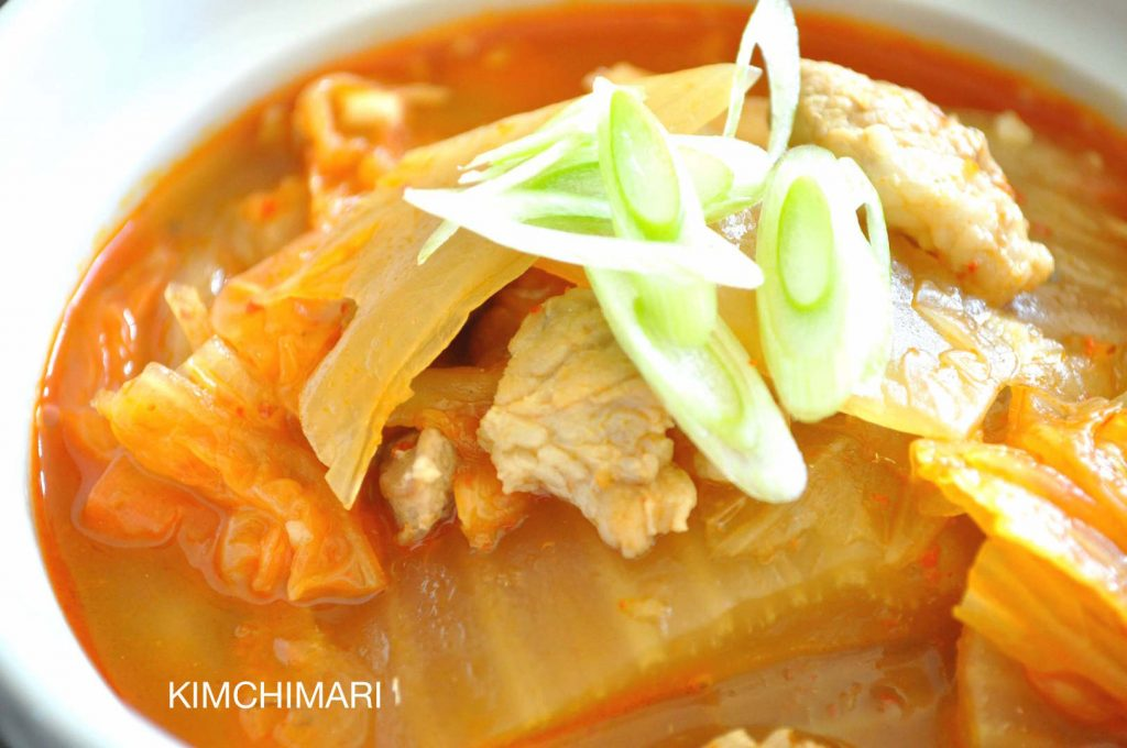close up of Kimchi Jjigae in white bowl garnished with fresh green onion slices
