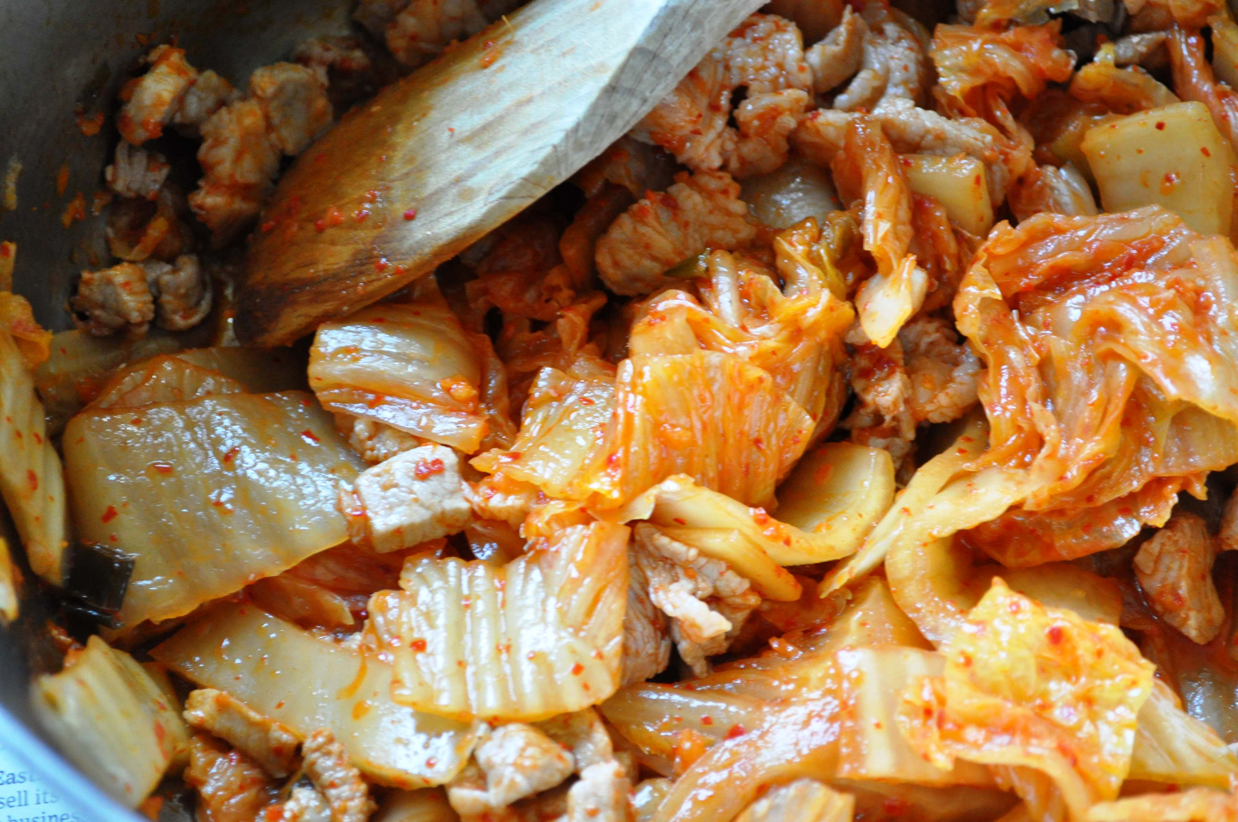 sauteeing kimchi and pork