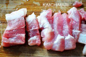 cut pork belly pieces on cutting board for kimchi jjigae