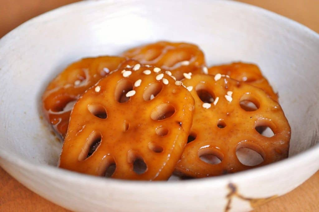 sweet and salty glazed lotus roots with sesame seeds garnish