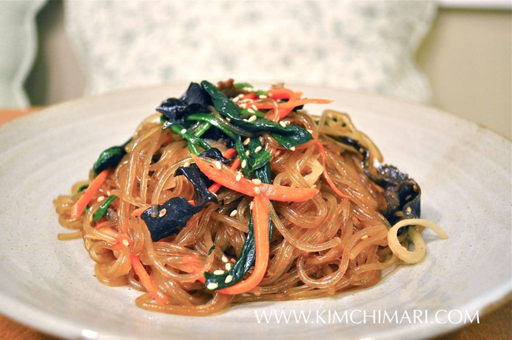 Japchae-Korean Glass Noodles plated with carrots spinach and noodles