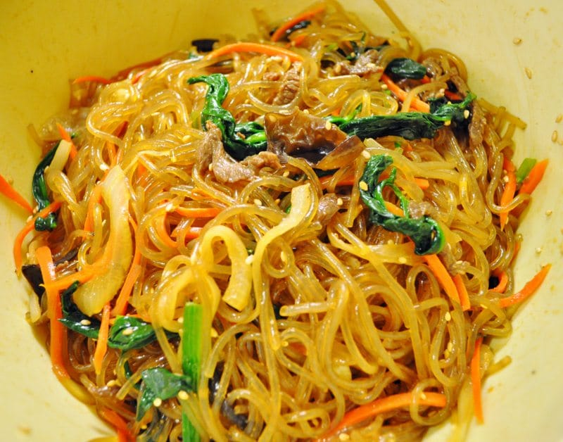 Japchae noodles all mixed in with vegetables, beef and seasoned in bowl