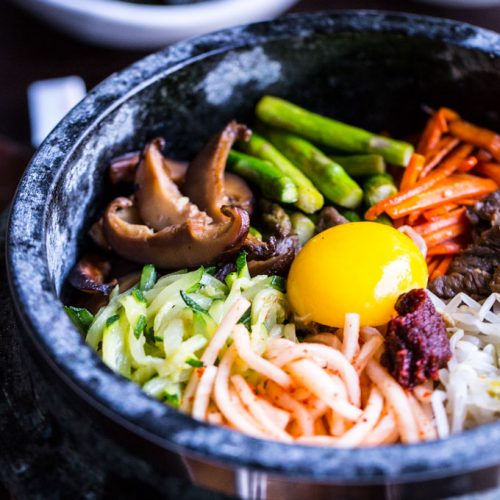 Bibimbap in Dolsot (Stone Pot) with vegetables and beef and egg yolk on top