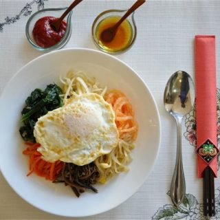 table setting of Bibimbap served with gochujang and sesame oil