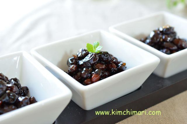 3 square bowls with glazed black beans with green leaf garnish