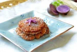 purple potato pancakes stacked on square plate garnished with slivers of raw potatoes