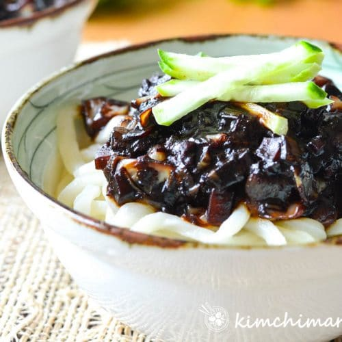 Jjajangmyeon noodles with black bean sauce in white bowl topped with cucumber garnish