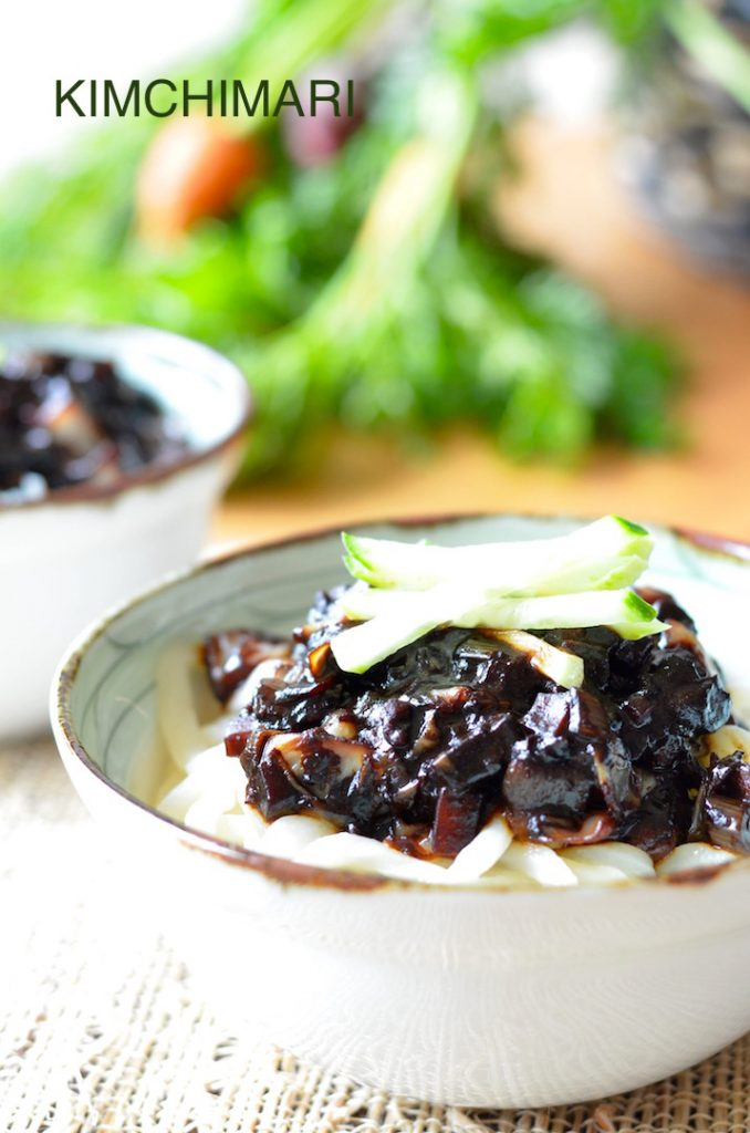 Jajangmyeon noodles served in a bowl topped with cucumbers