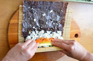 hold the mat with your thumbs while pressing the stuffing onto rice