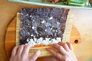 wind the mat over onto the gimbap, while pressing firmly