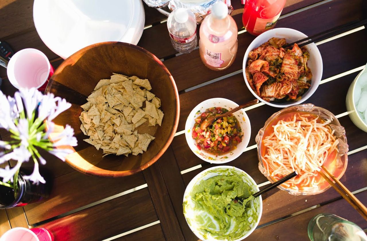 Party table with Chips, Guacamole and Salsa, Moosaengche, Kimchi