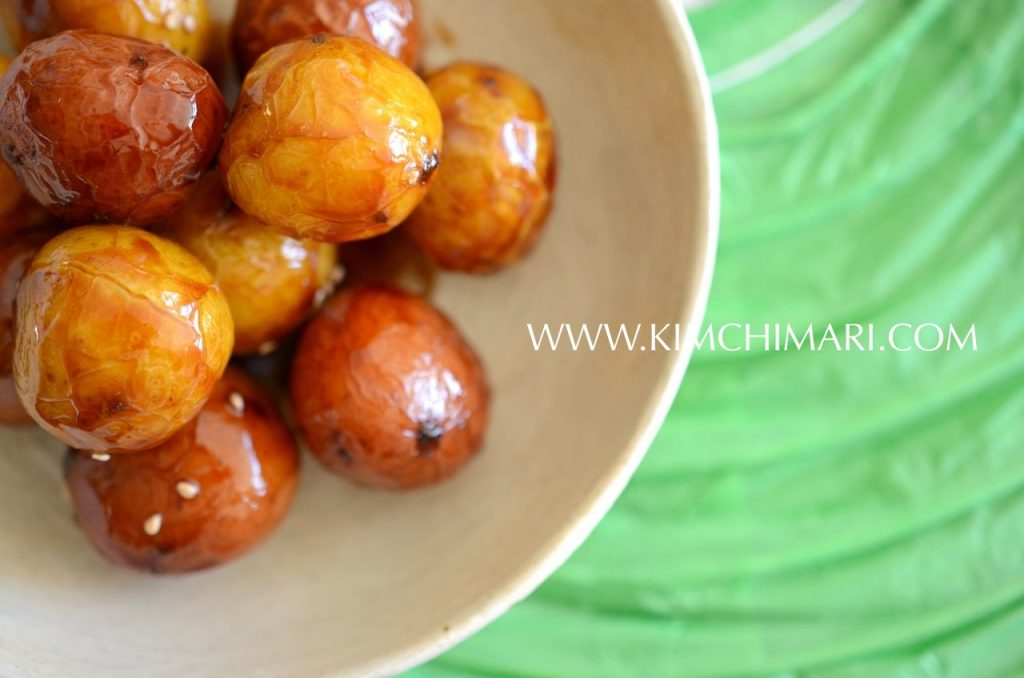 Soy sauce glazed shiny baby potatoes in a bowl on green paper background