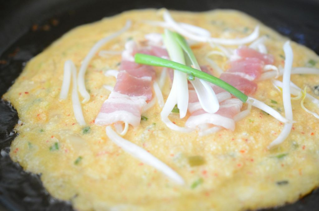 Bindaetteok cooking in pan