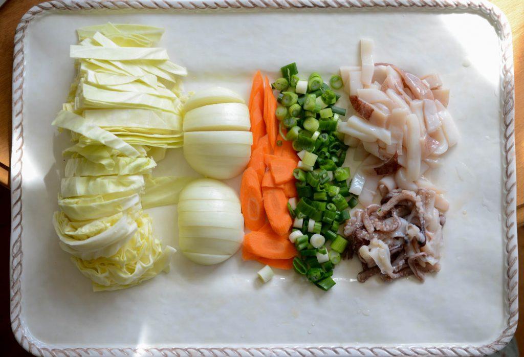 Zutaten für die scharfe Tintenfisch-Pfanne: Kohl, Zwiebeln, Karotten, grüne Zwiebeln und Tintenfisch