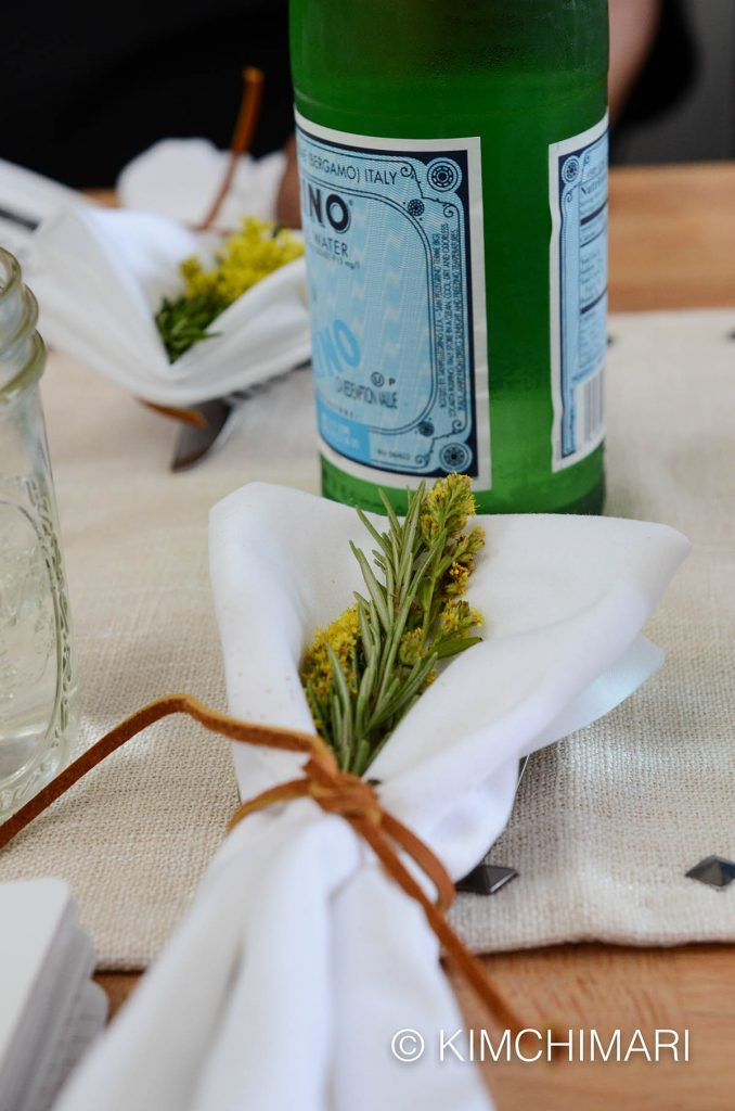 place setting with rosemary in napkin