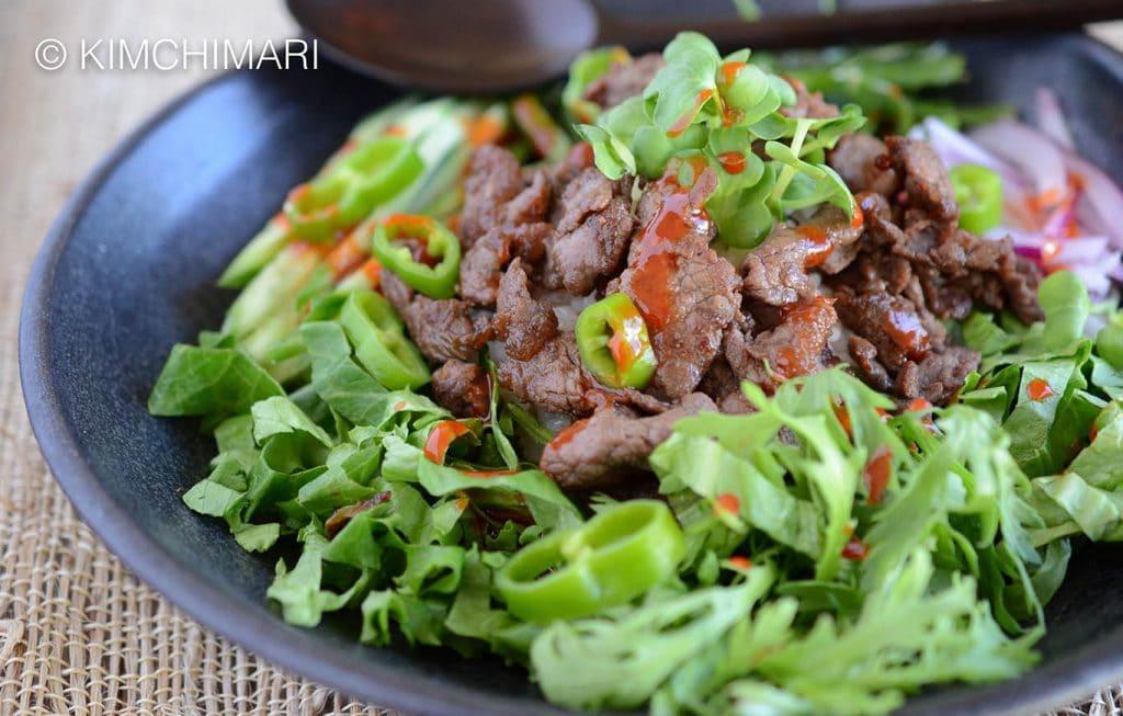 Bulgogi Rice Bowl with fresh greens topped with Gochujang sauce