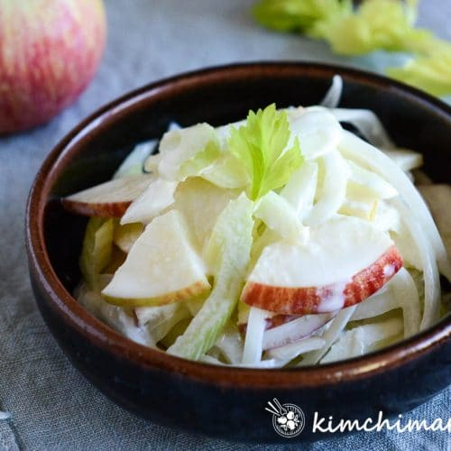 creamy apple onion celery salad plated in brown shallow bowl on blue cloth