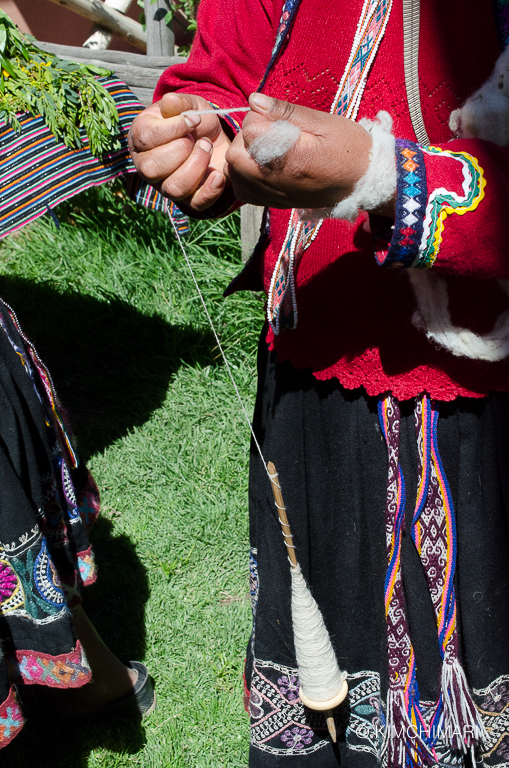 Peruvian lady pinning Alpaca hair into yarn