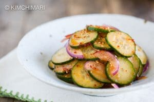 Spicy Asian Cucumber Salad with onions finished and shown in white bowl