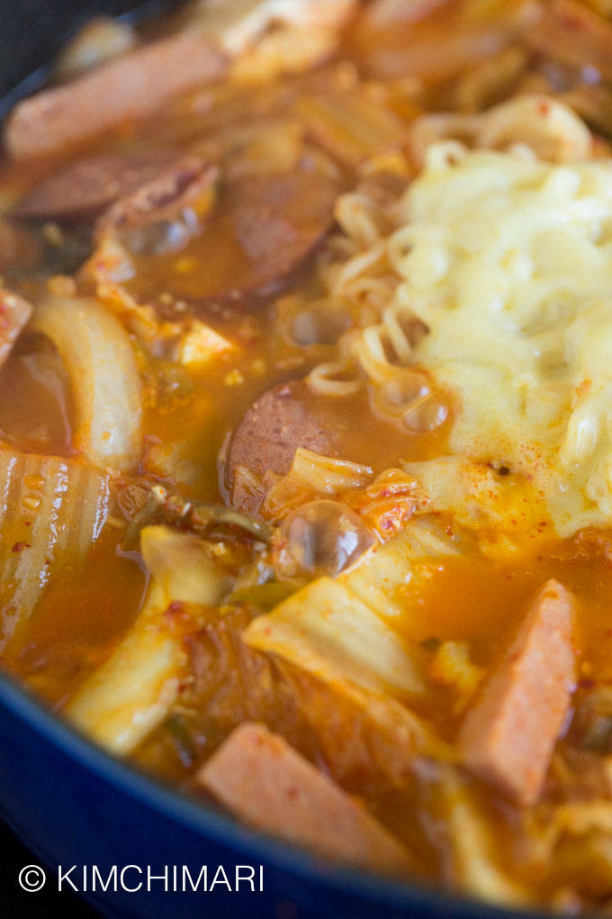 Close up of Budae Jjigae boiling and bubbling with cheese melting