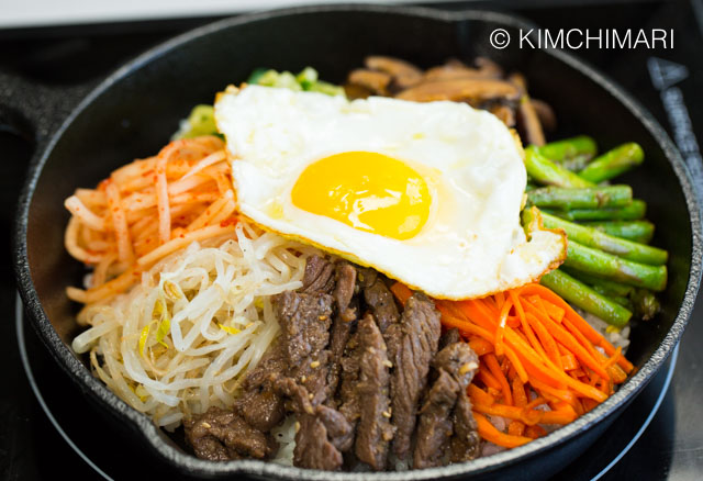 Bibimbap in 8 inch cast iron pan with fried egg on top of vegetables and beef