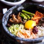 bibimap in grey stone pot with raw egg yollk and gochujang on top