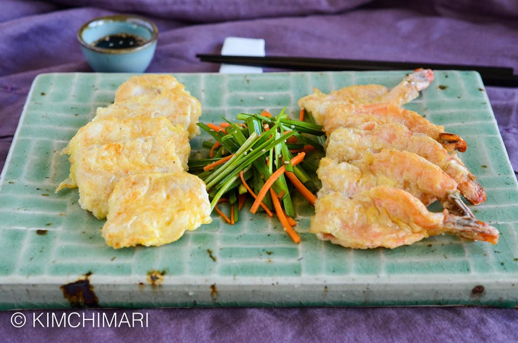 fish and shrimp jeon plated on green rectangular plate with chive salad in center