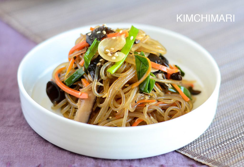 japchae glass noodles in white bowl on light purple linen