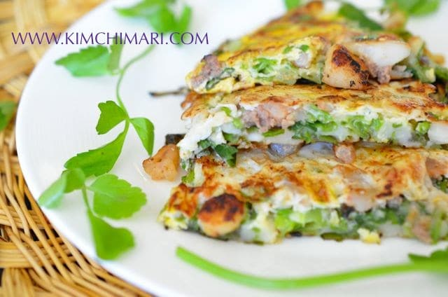 Pajeon Korean Scallion Seafood Pancake on white plate garnished with minari