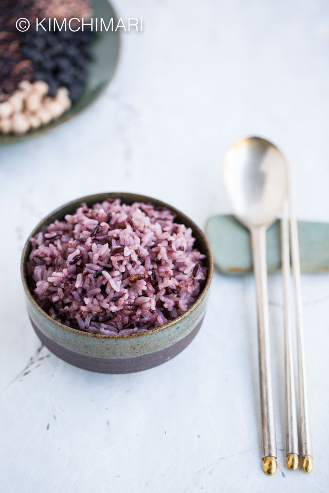 Korean purple rice in bowl with silver spoon and chopsticks