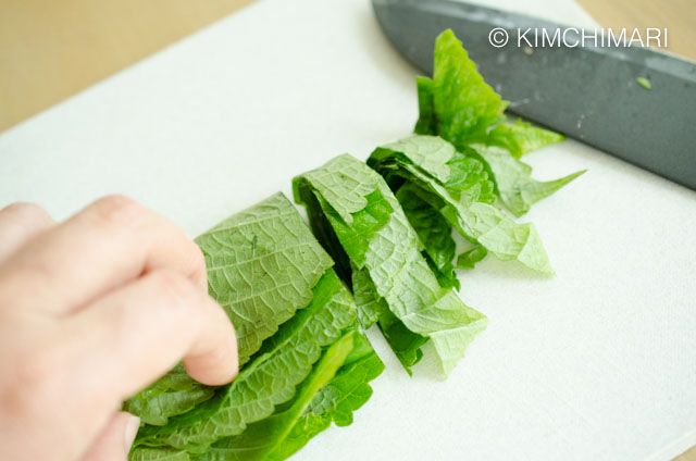 Cutting perilla leaves into thick strips with knife on cutting board