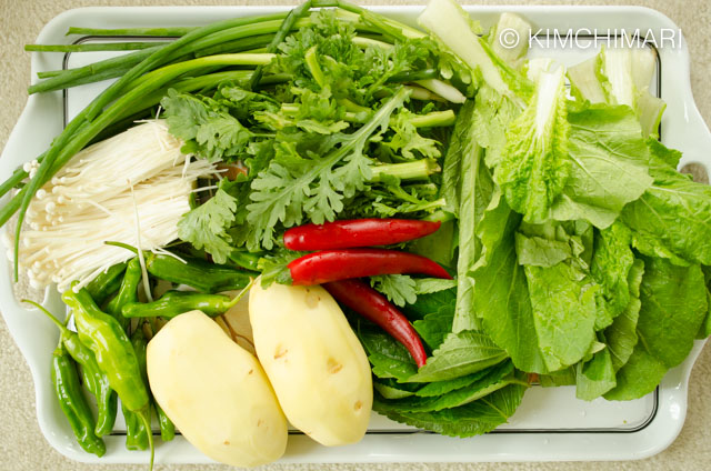 Veg ingredients of green onions, potatoes, chili peppers, perilla leaves laid out on tray