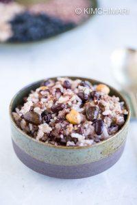 Cooked korean multigrain rice in ceramic bowl with silver spoon