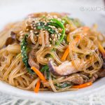 Japchae served in white bowl