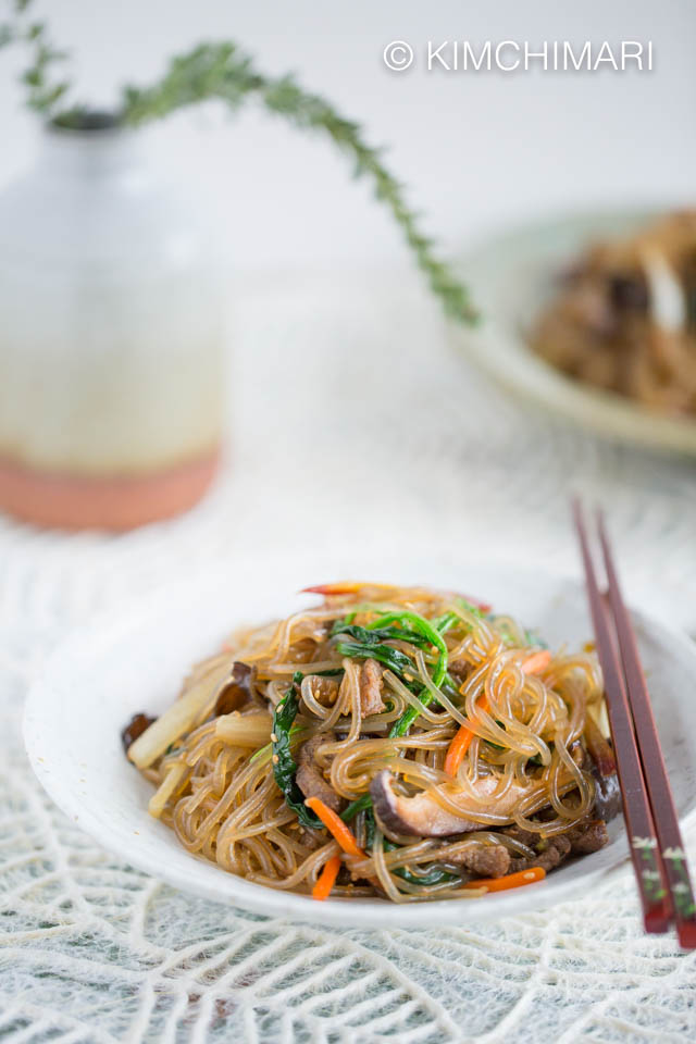 Japchae served with chopsticks on white table cloth