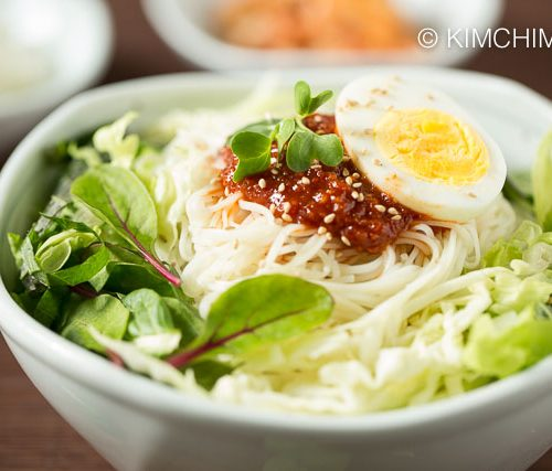 Bowl of bibim guksu served with fresh vegetables , topped with gochujang sauce and egg