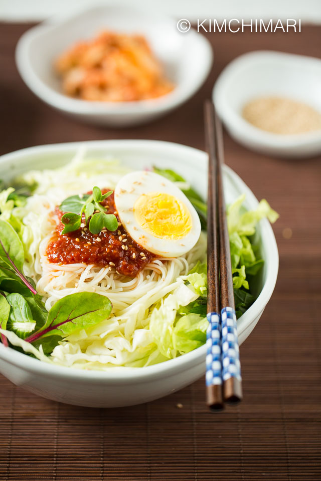 Bibim Guksu served in bowl with vegetable toppings and a side dish of kimchi