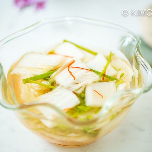 closeup of nabak kimchi in glass bowl with a place setting of spoon