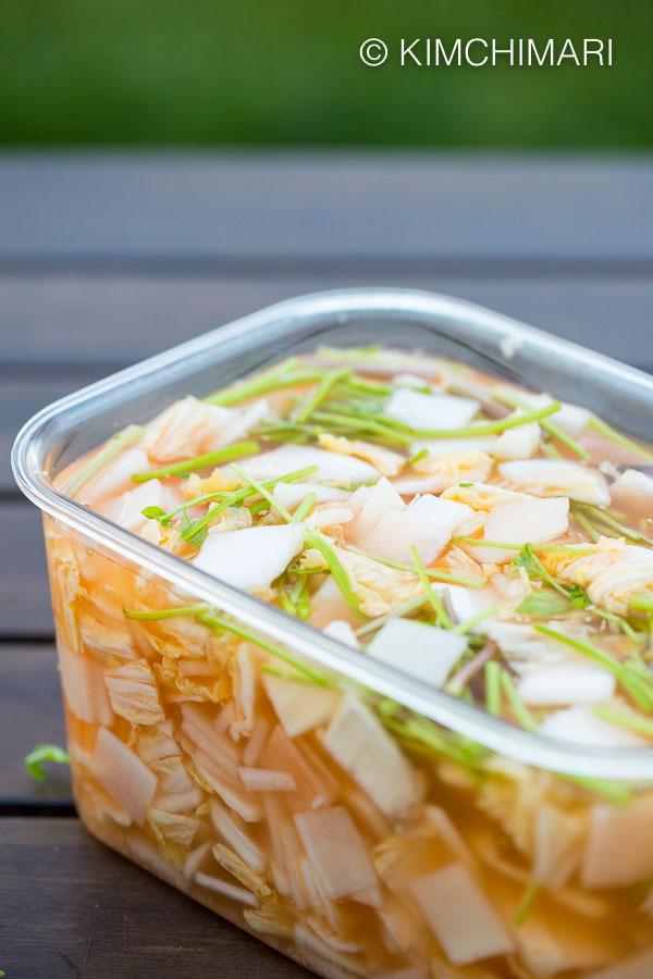 whole rectangular plastic container full of nabak mul kimchi