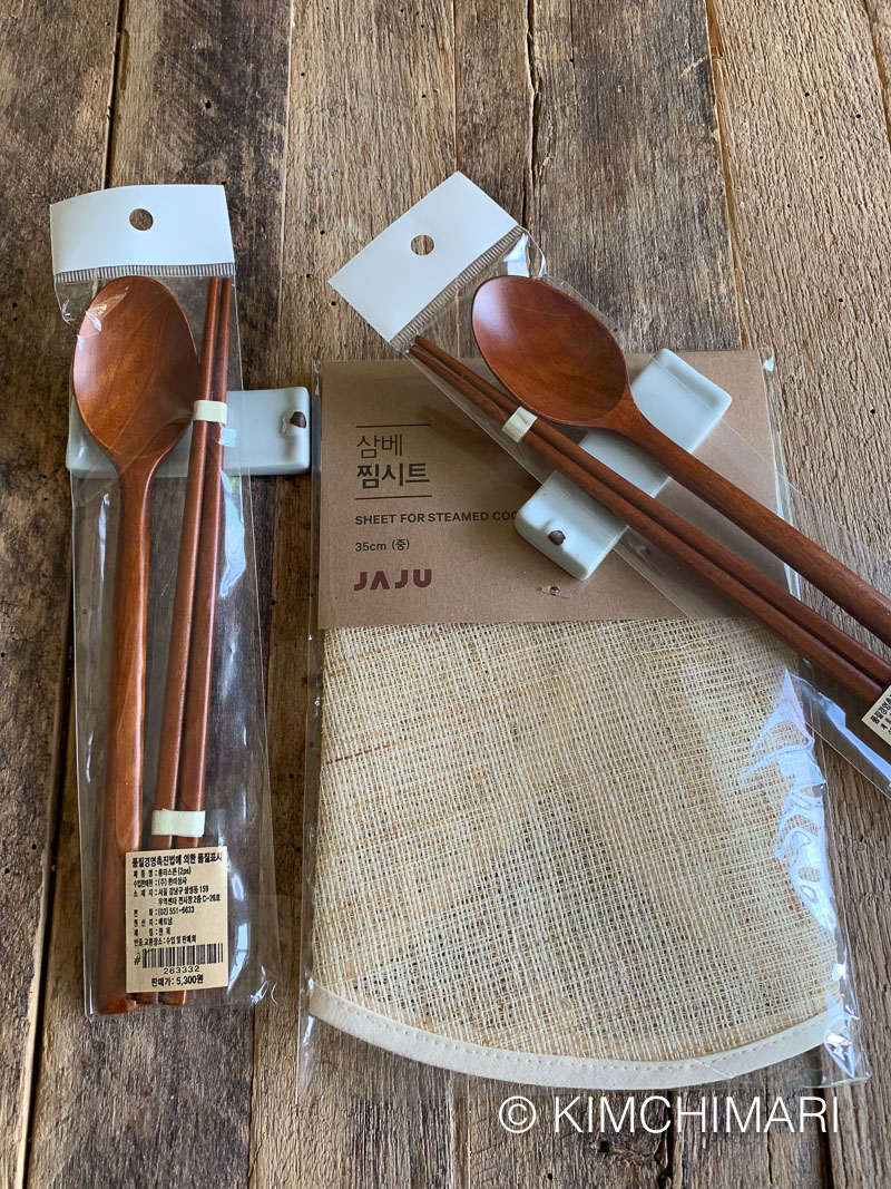 wooden spoons chopsticks on spoon rest and hemp cloth steam sheet packaged laid out on wooden board