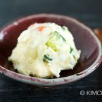 potato salad served as a scoop using ice scream scooper on red ceramic bowl