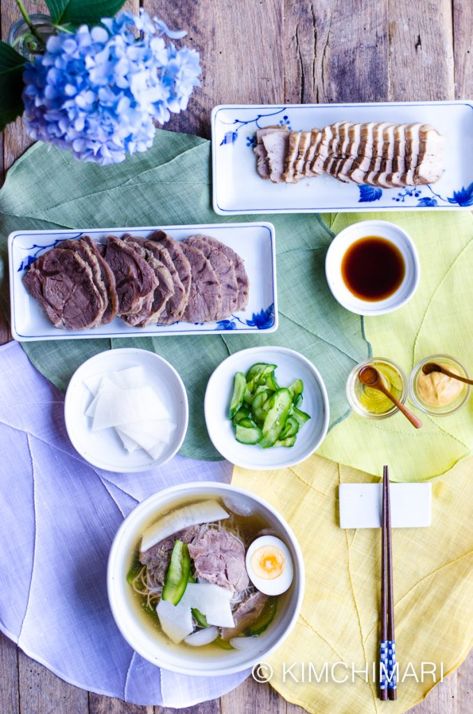 table setting example of korean cold noodle soup with samgyeopsal and vinegar and mustard