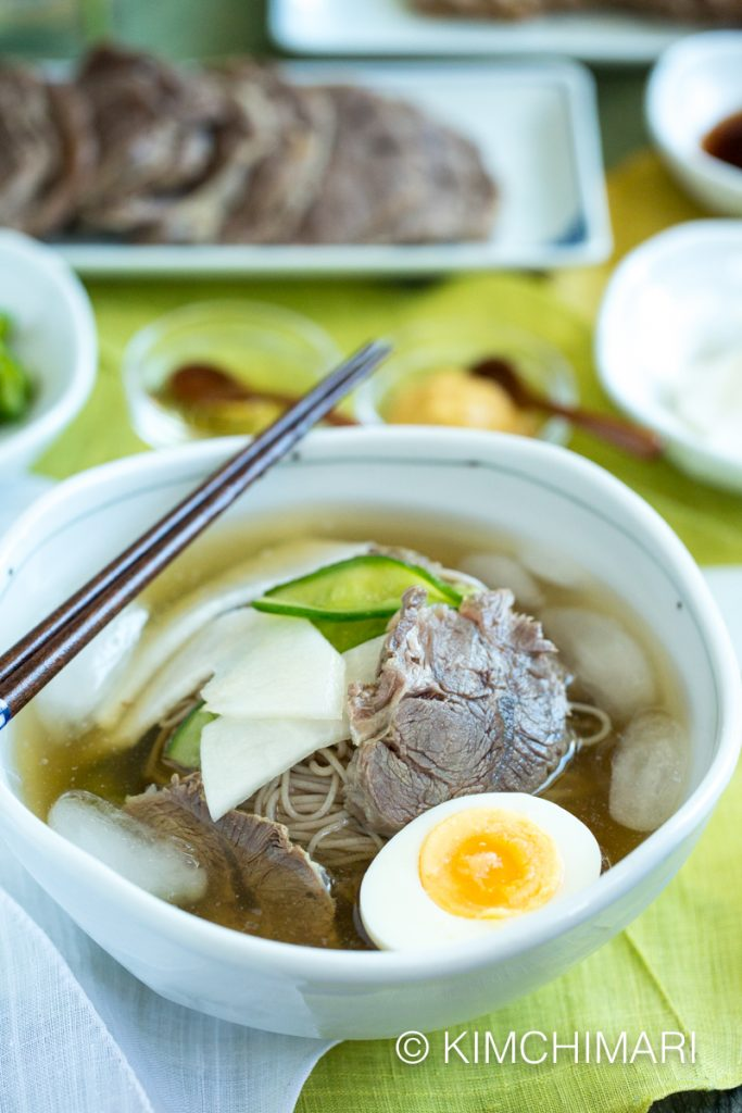 Mul Naengmyeon served in white bowl with toppings, and sliced beef in the background