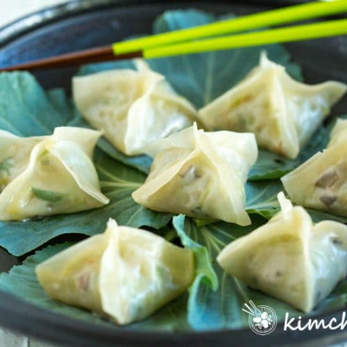 Korean Vegetarian Dumplings on black plate lined with fresh kale leaves