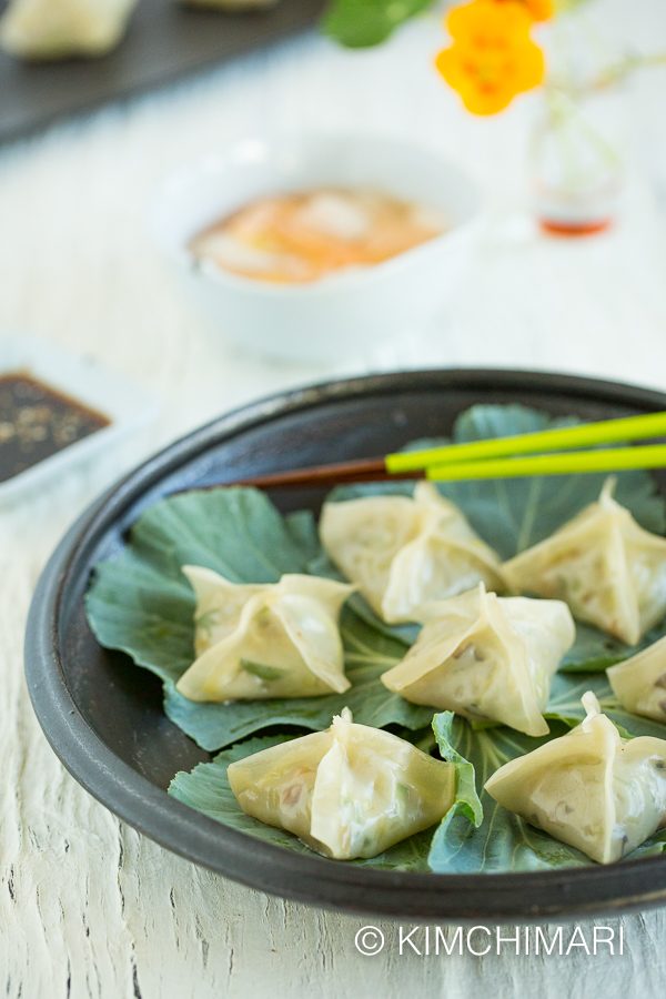 Steamed dumplings presentation with dipping sauce and nabak kimchi in the back