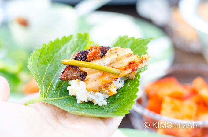 ssam on palm of hand with rice and grilled samgyeopsal, kimchi, ssamjang and garlic scape jangahjji
