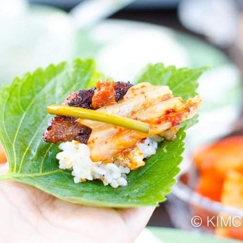 perilla leaf on hand piled with rice, pork belly, kimchi and ssamjang