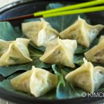 Vegetarian Dumplings or Pyeonsu served on kale leaves on black plate with green chopsticks
