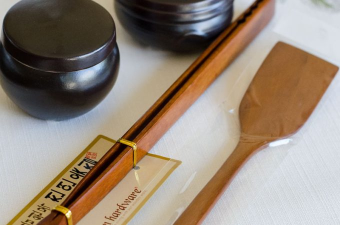 wooden tongs spatula and korean mini clay jars on white place mat